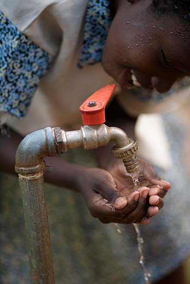 girl getting water from tap image